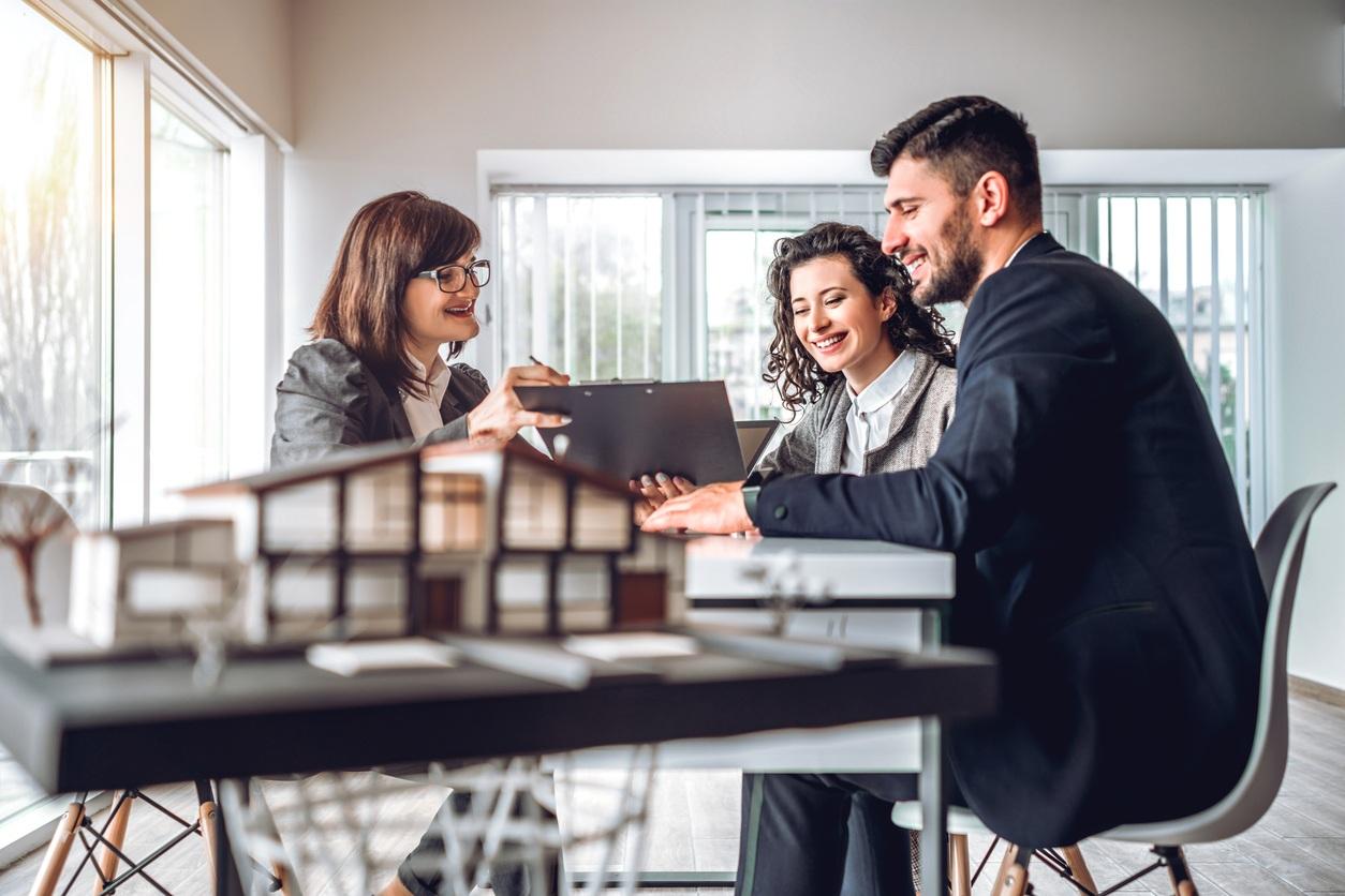 Agente inmobiliario mostrando planos de una vivienda