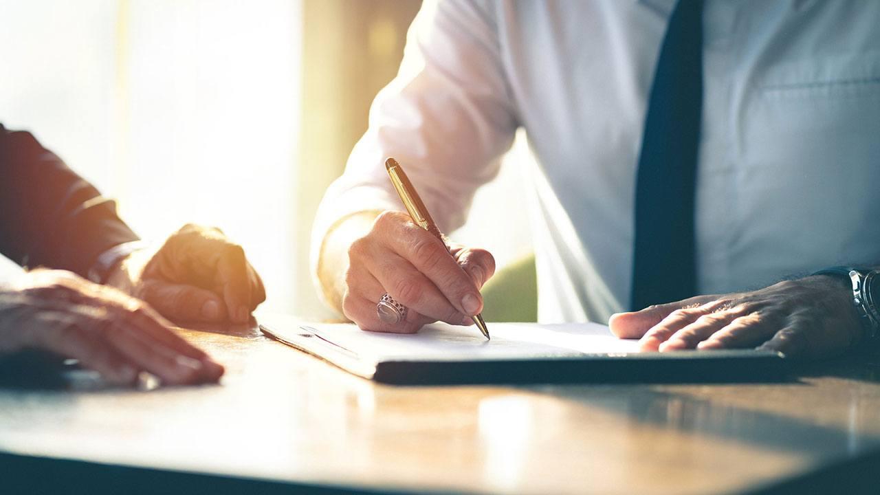 Persona firmando la solicitud de un crédito hipotecario