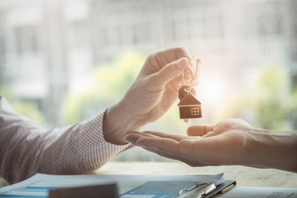 Persona enregando llaves de una casa nueva