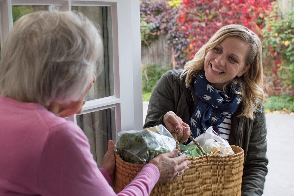 Una vecina llevándo verduras a una señora